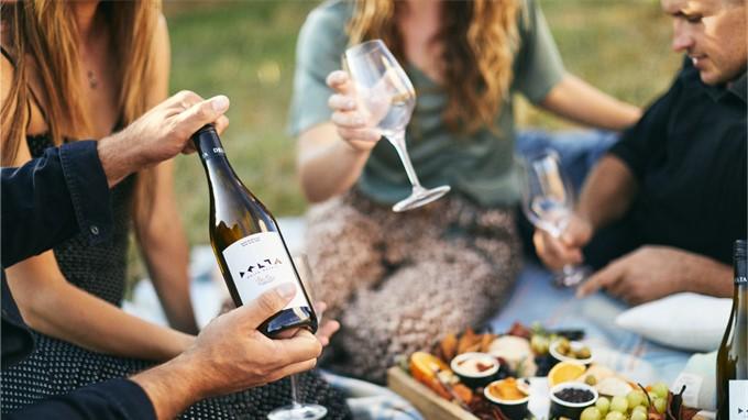 Mann oeffnet Weinflasche mit Drehverschluss bei Picknick